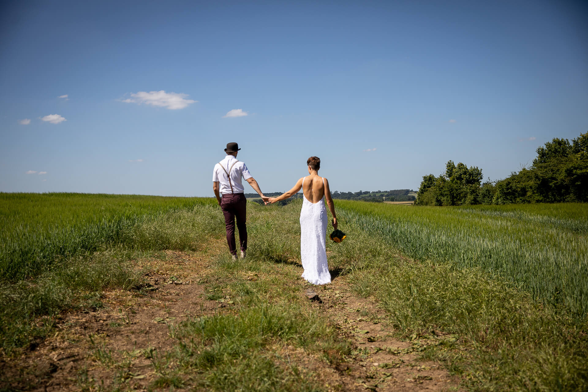 Smiling, relaxed couple walking in a field on their wedding day, at Love2yurt, Wedding Photography Kent