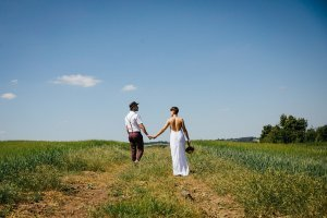 Smiling relaxed married couple walking in a field after their DIY wedding ceremony