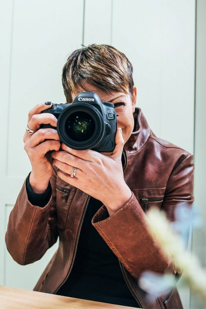 female photographer holding camera to face smiling