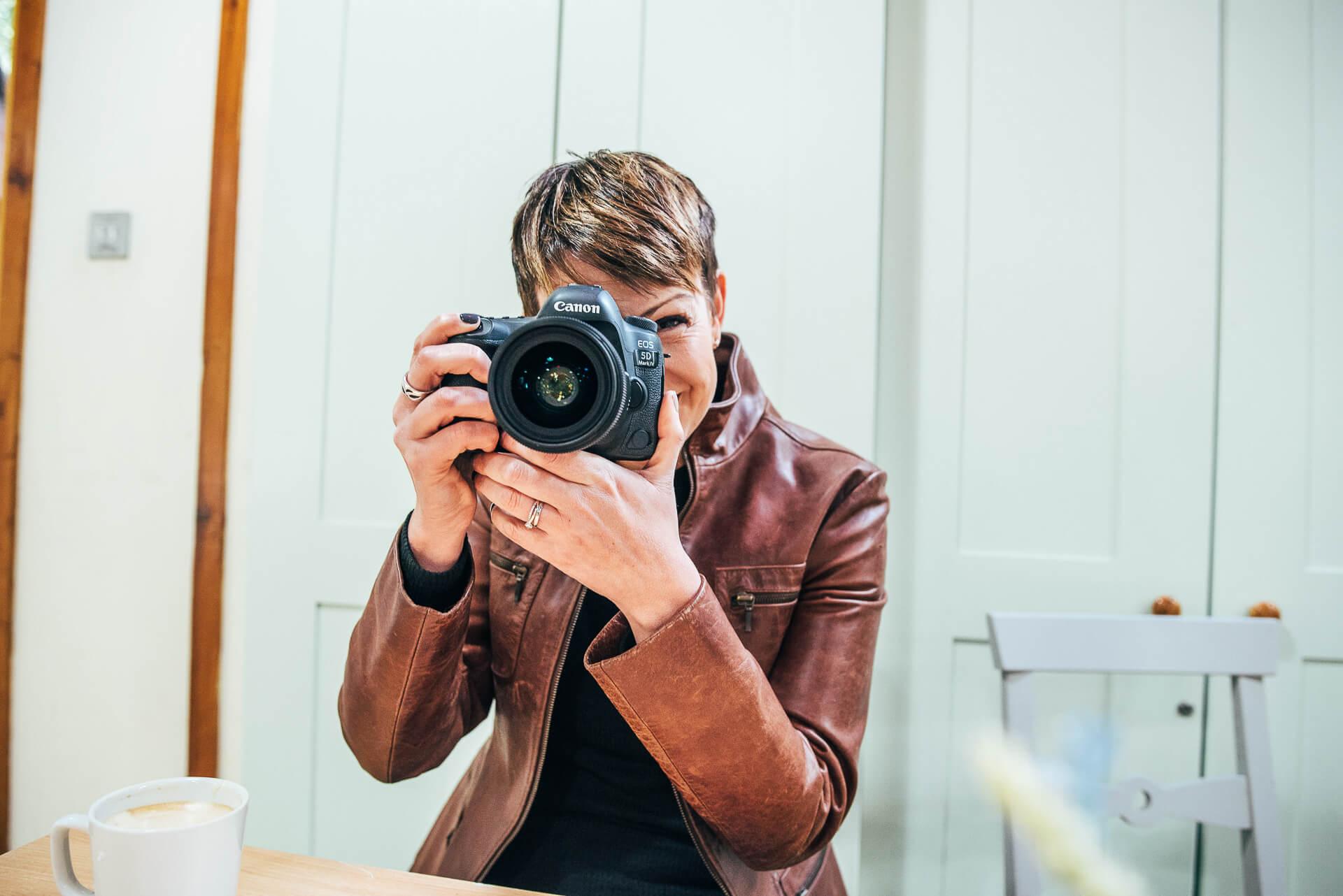Nicola Dawson, Kent Wedding photographer seated in woodland with her camera