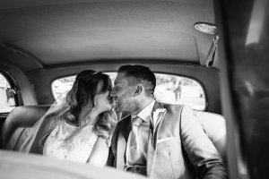 Married couple kissing in the back of their wedding car arriving at Blake Hall Wedding venue