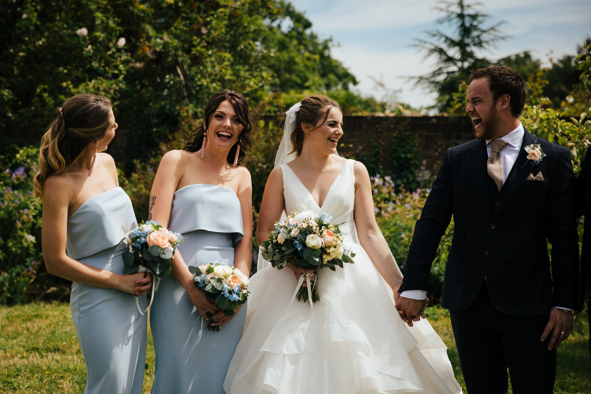 Bridal party laughing in a group shot at Ratsbury Barn Kent, Wedding Photography