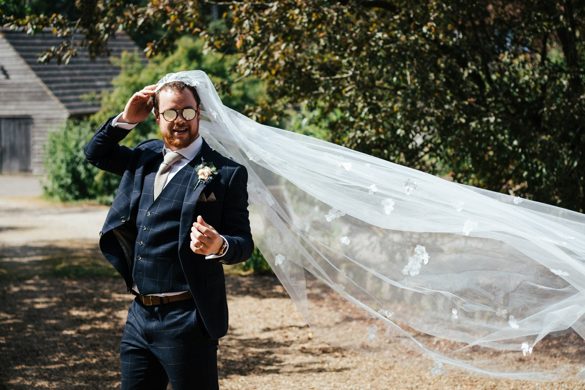 Groom wearing his brides veil after the ceremony