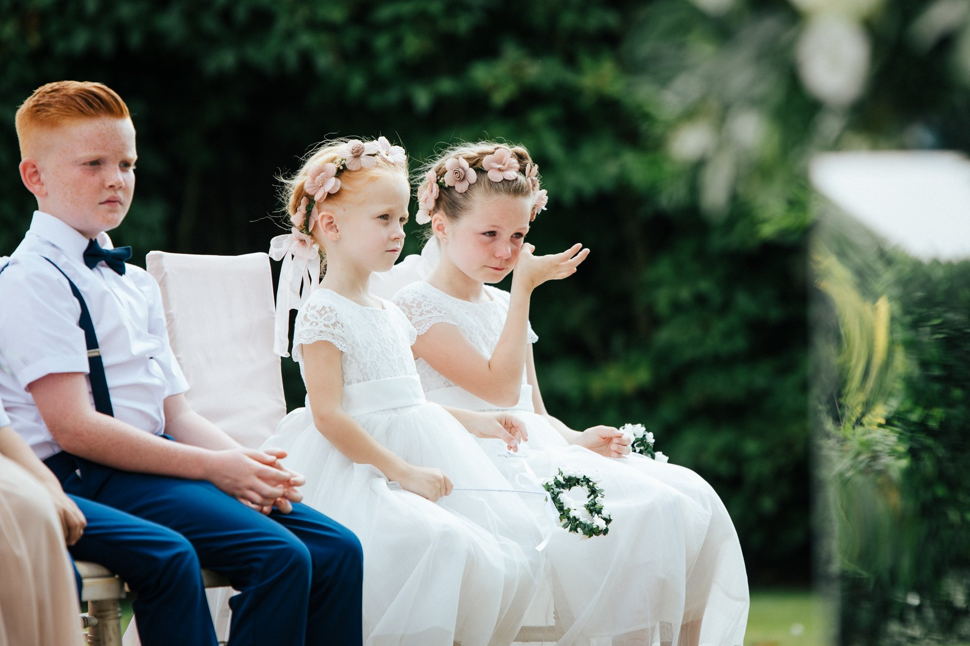 Natural moment capturing a bridesmaid wiping a tear away