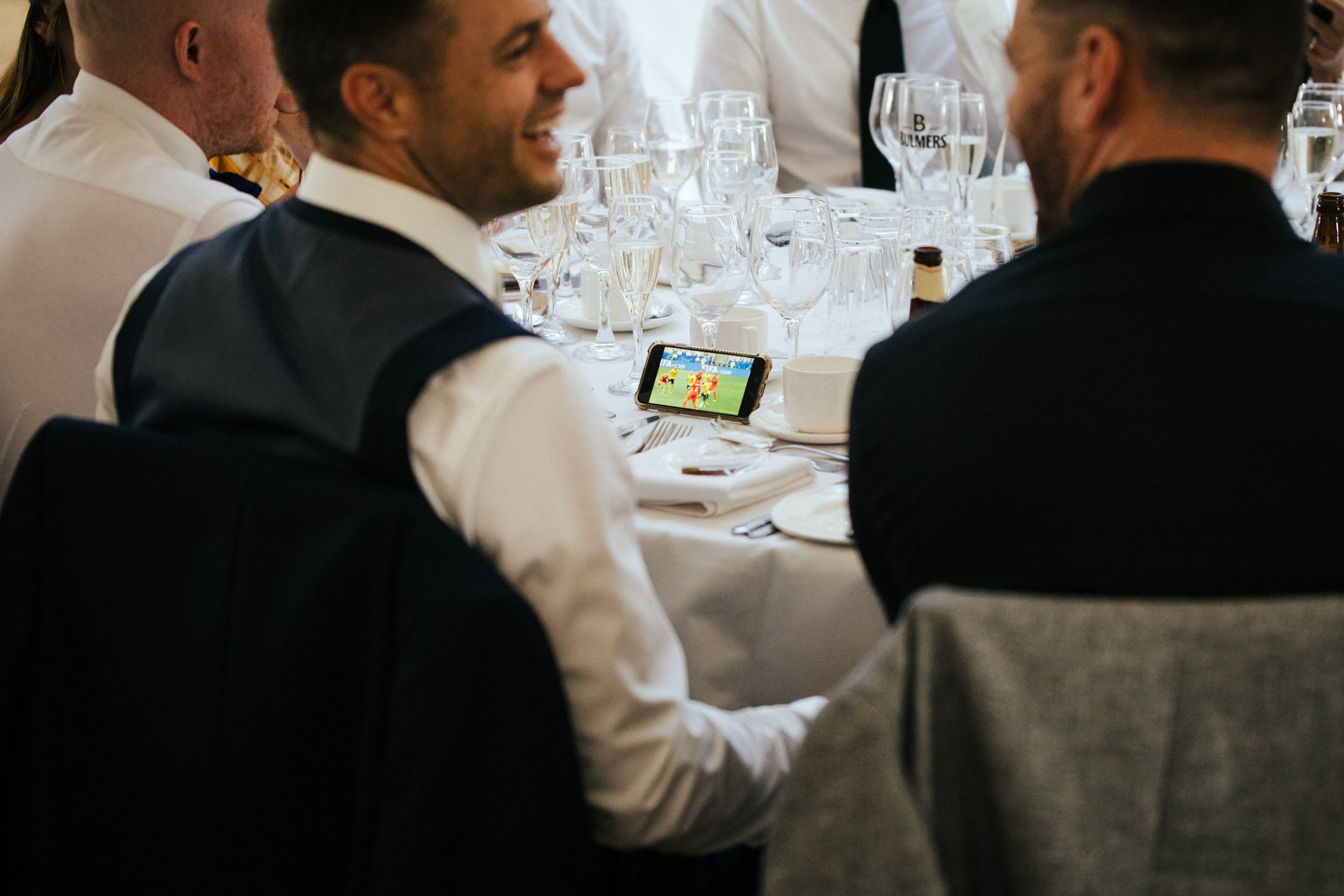wedding guests watching football during speeches
