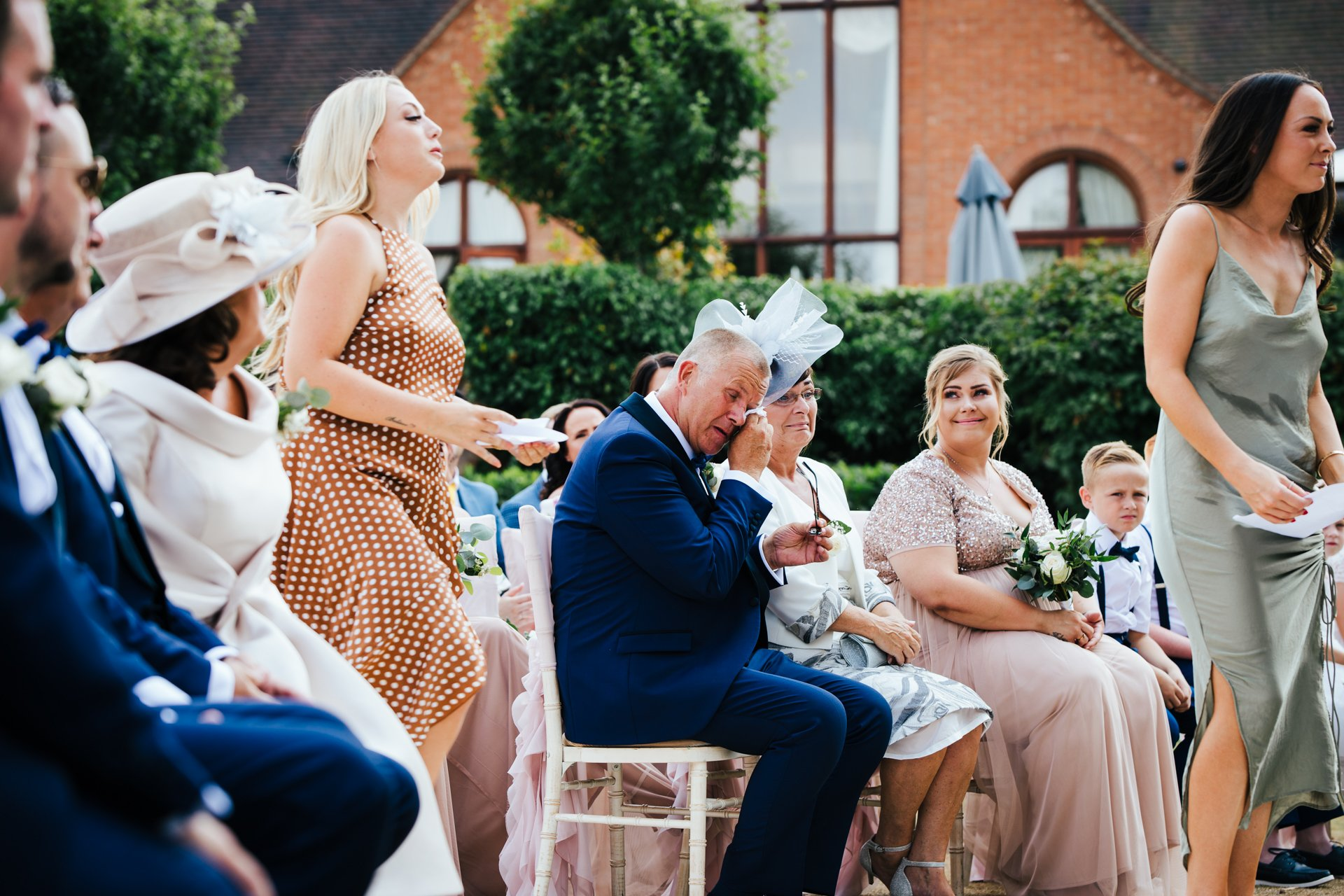 Father of the bride wiping his eyes watching his daughter wed