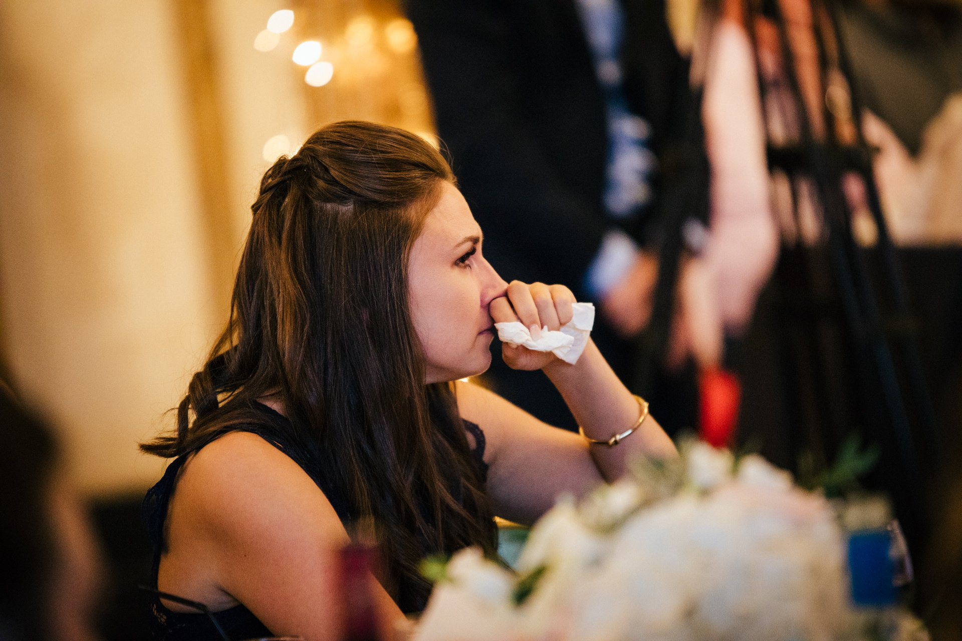 wedding guest wiping her eye during speeches