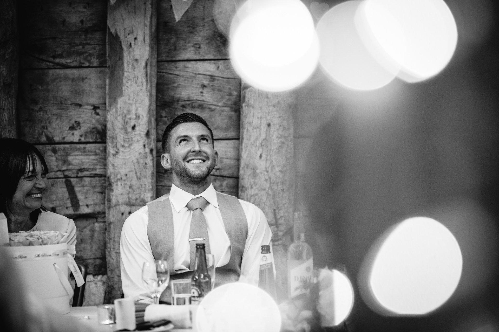 Groom looking embarrassed during wedding speeches