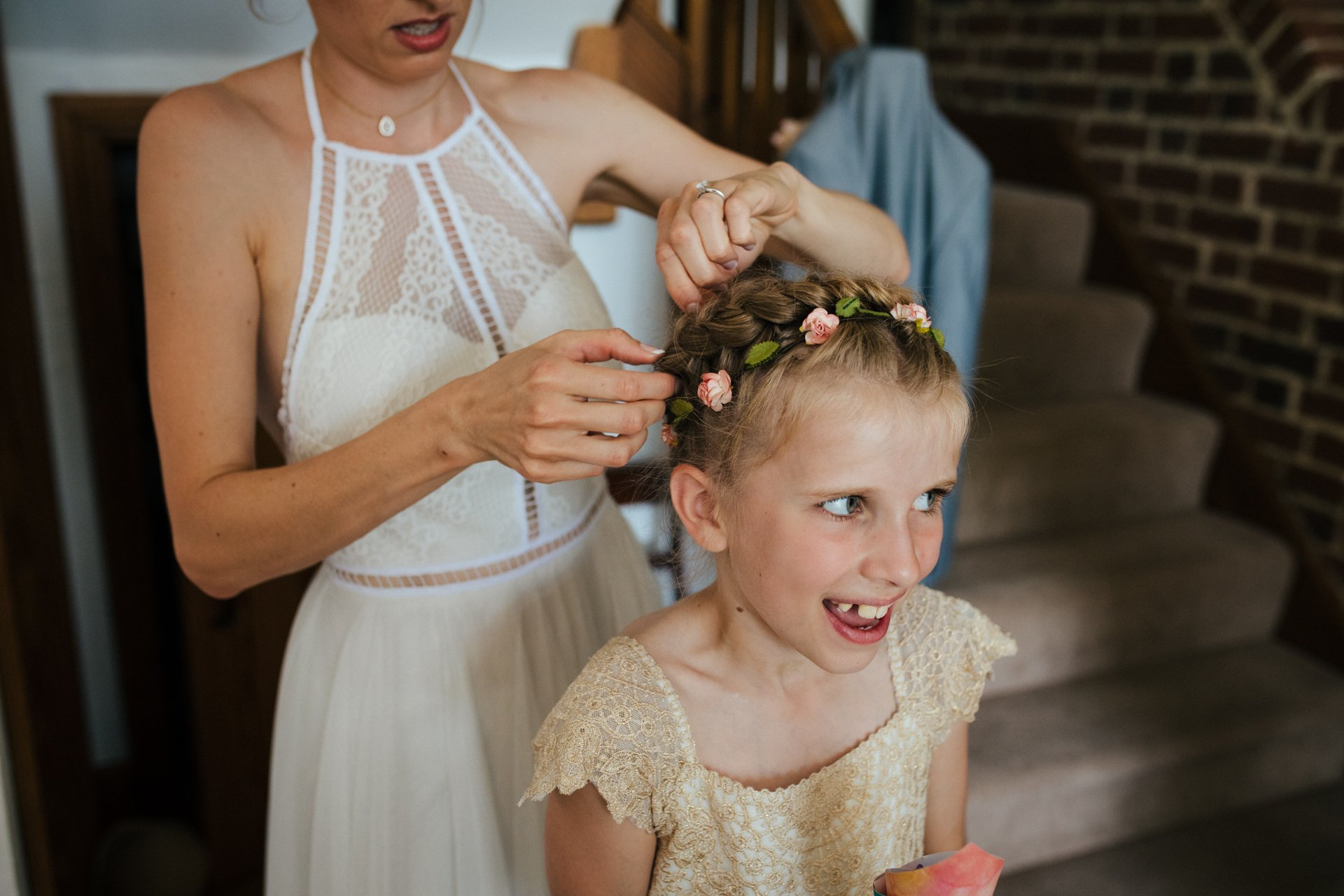 Bridesmaid having her hair pinned up before wedding ceremony
