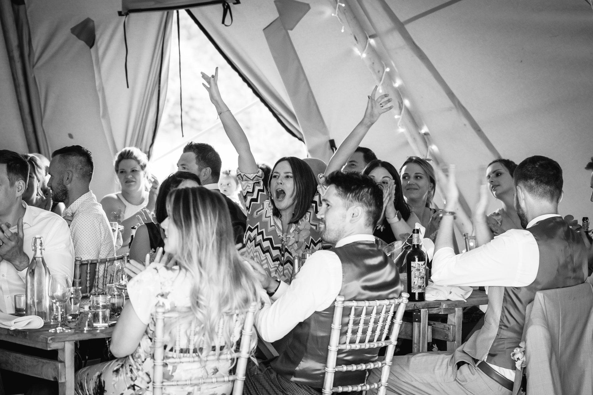 Wedding guest raising arms during wedding speeches