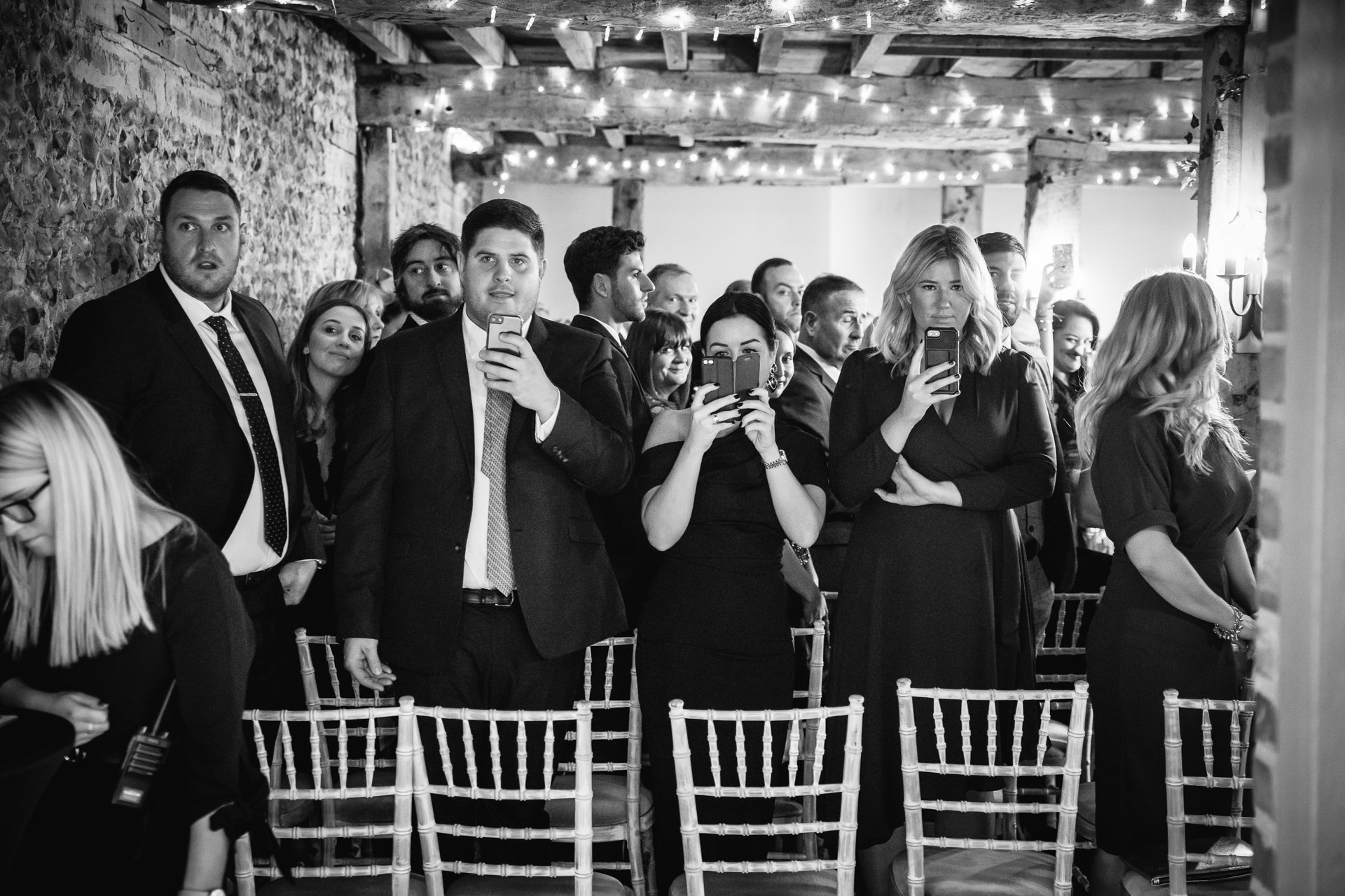 wedding guests all with phones watching bride walk down the aisle