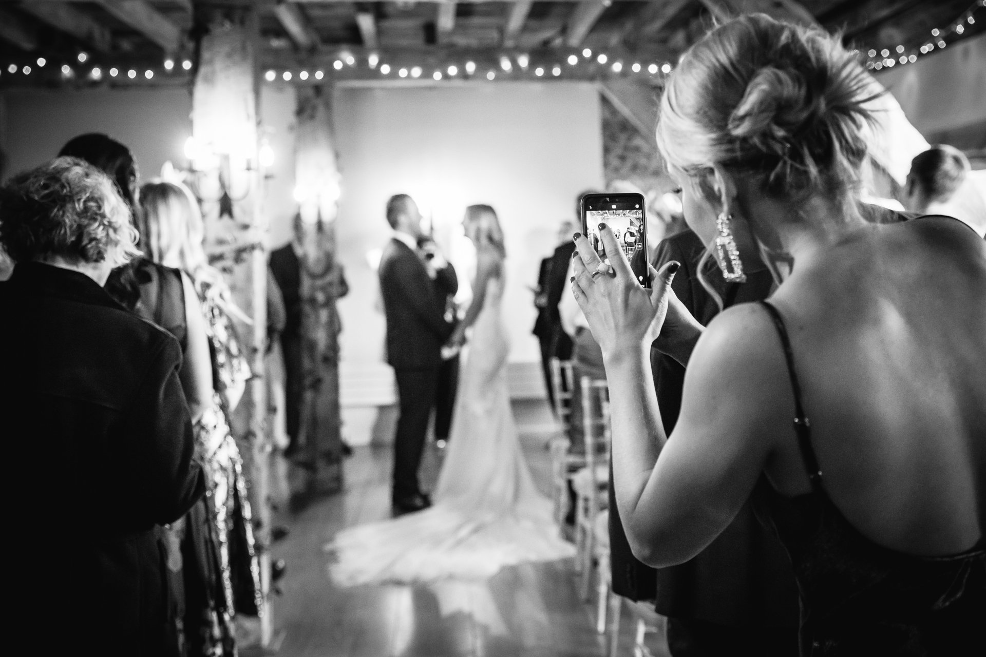 guest takes phone photo of bride and groom during the ceremony