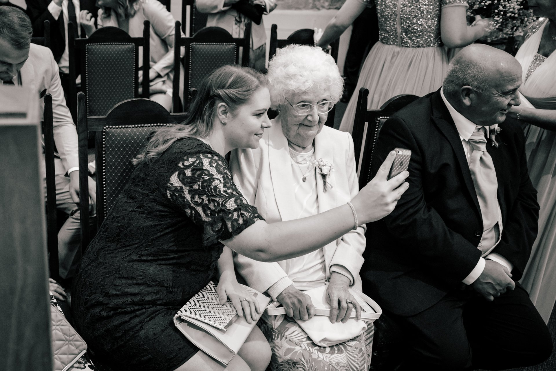 wedding guest takes a selfie with grandparent during wedding ceremony