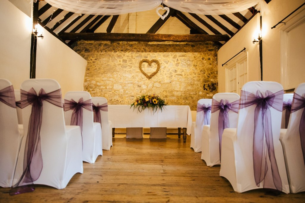 The buttery at The Bull Hotel Wrotham, wedding venue styled with white chair covers with purple sashes and bright floral arrangement