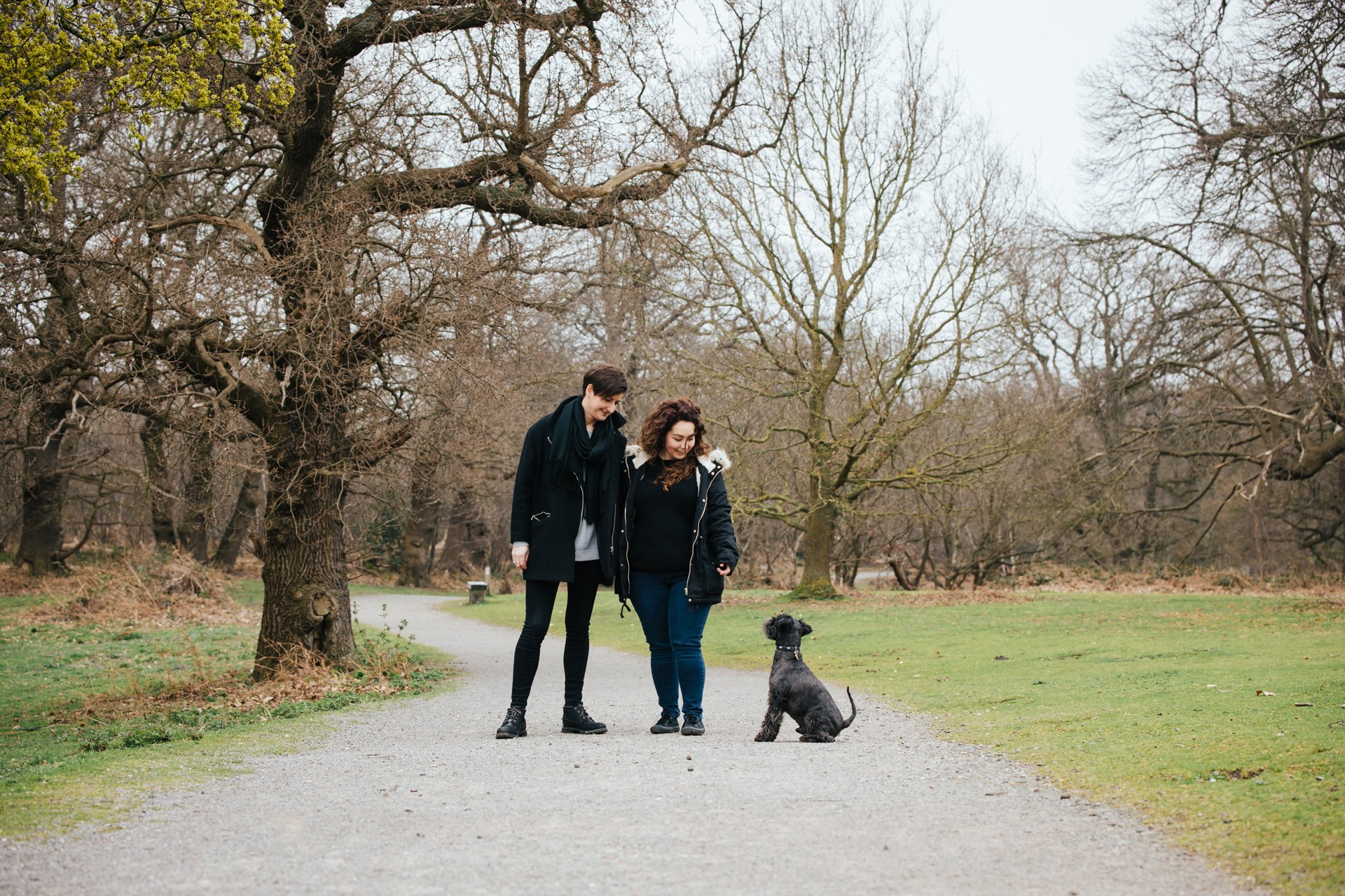Two gorgeous ladies smiling with their dog during their engagement shoot in a woodland setting in Kent