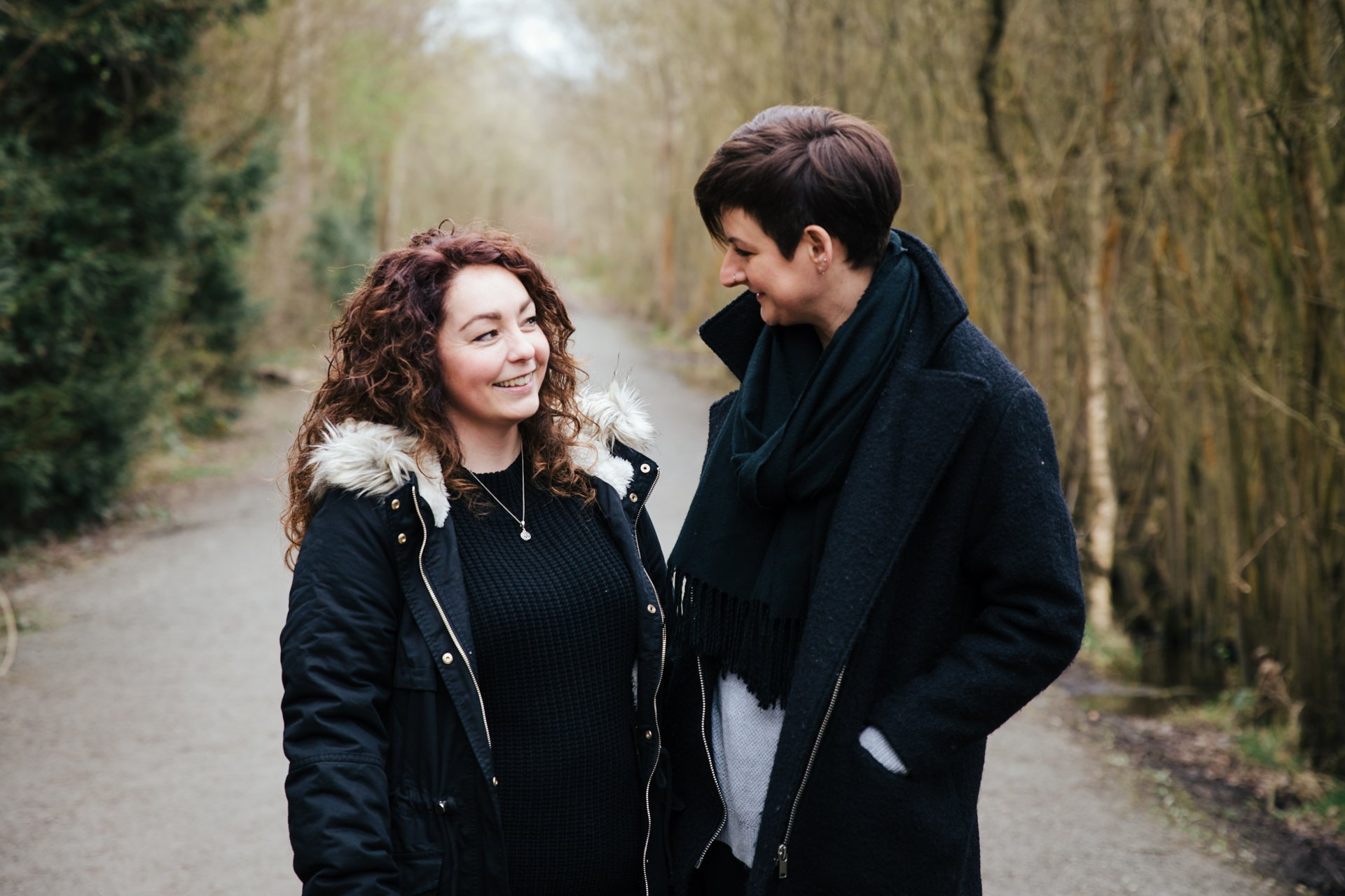 Two gorgeous ladies smiling during their engagement shoot in a woodland setting in Kent