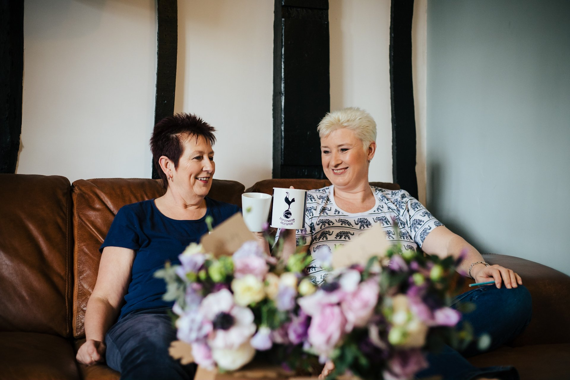 Two brides laughing and having a cup of tea during bridal preparations at The Bull Hotel