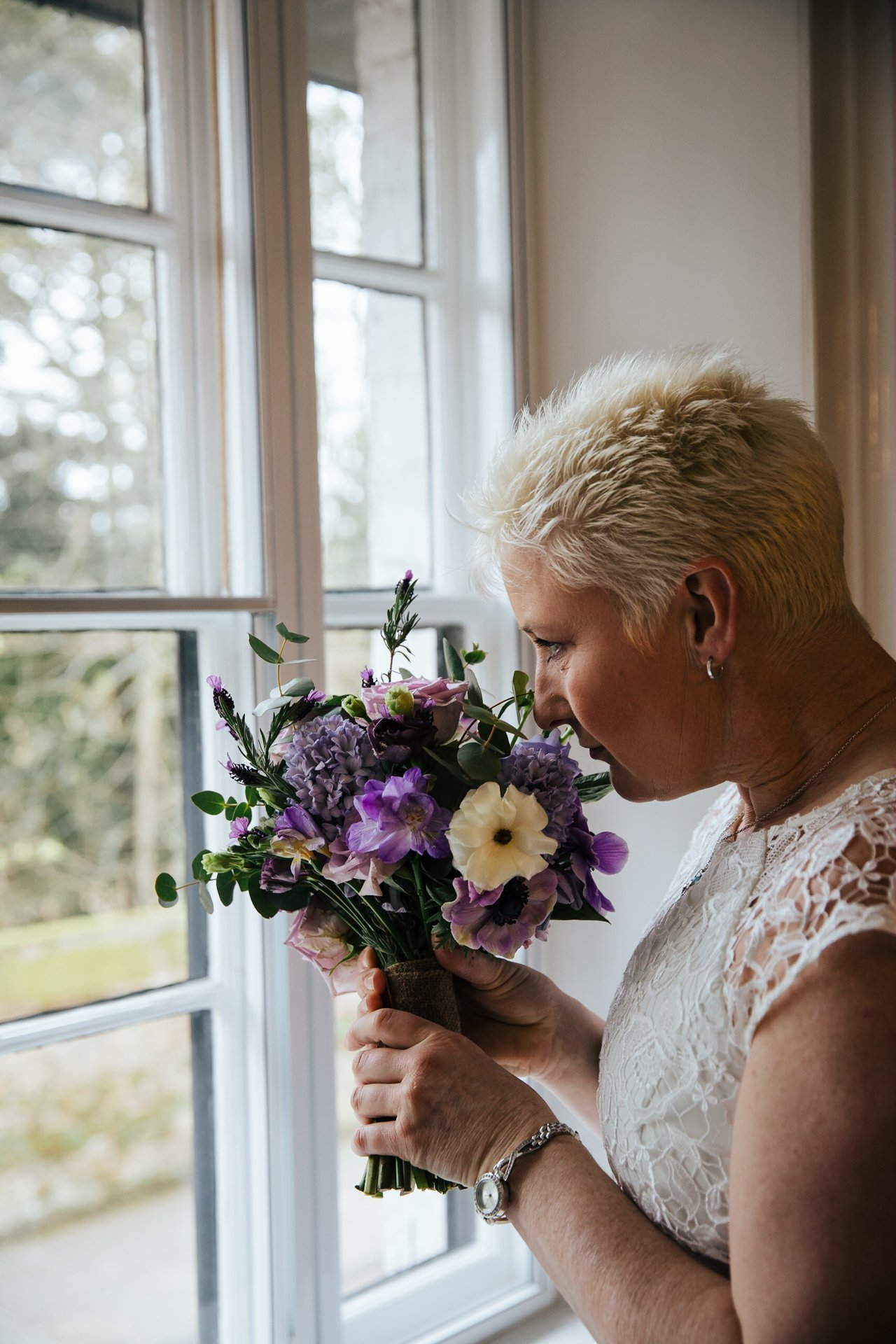 Bride smiling her bouquet before her wedding ceremony