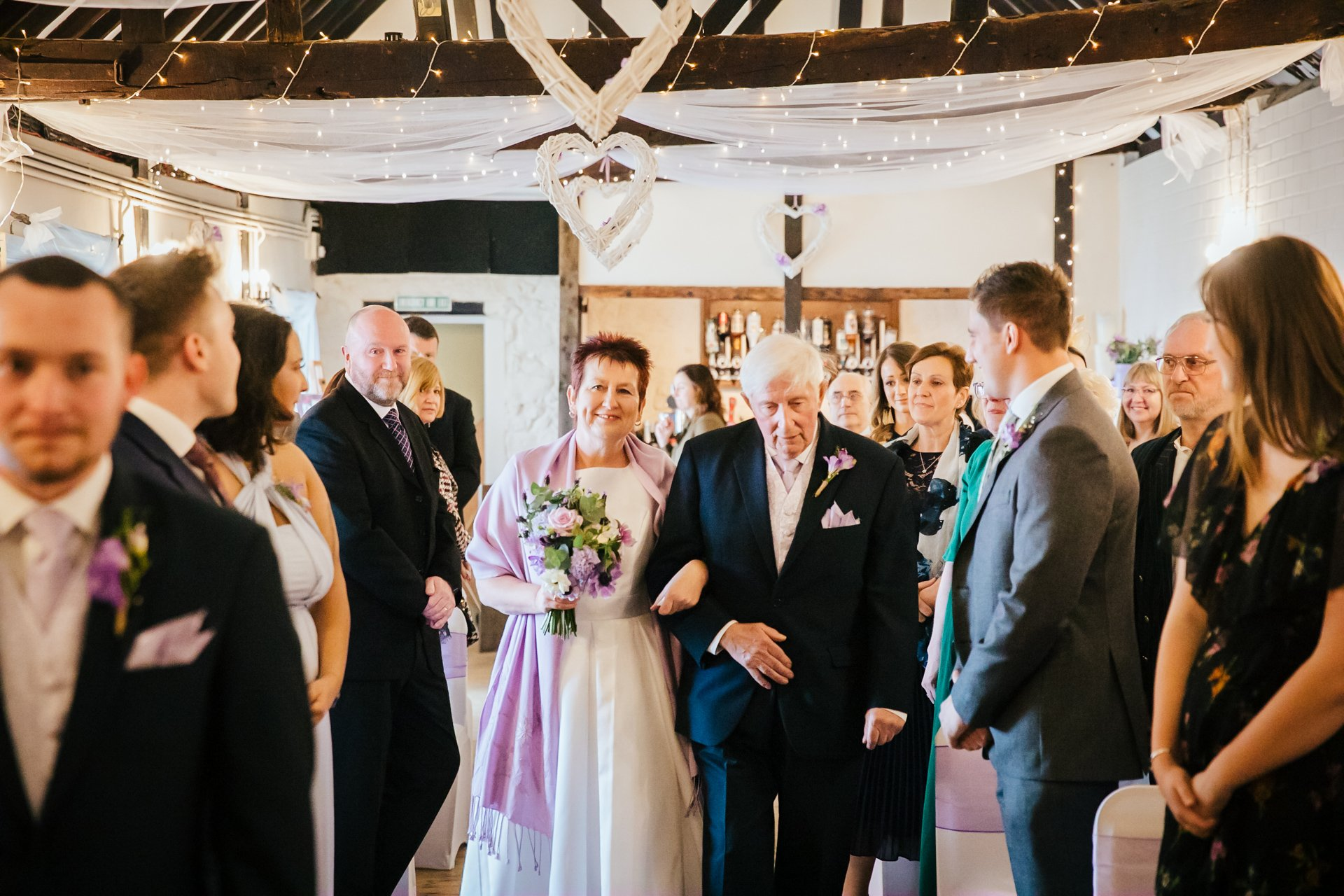 Bride being walked down the aisle in The Buttery at The Bull Hotel, Wrotham, Kent