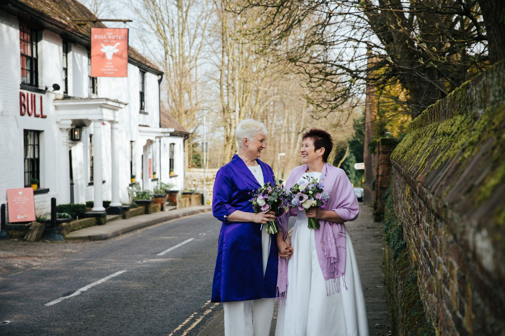 Two brides happy and smiling at each other outside their Kent wedding venue, The Bull Hotel