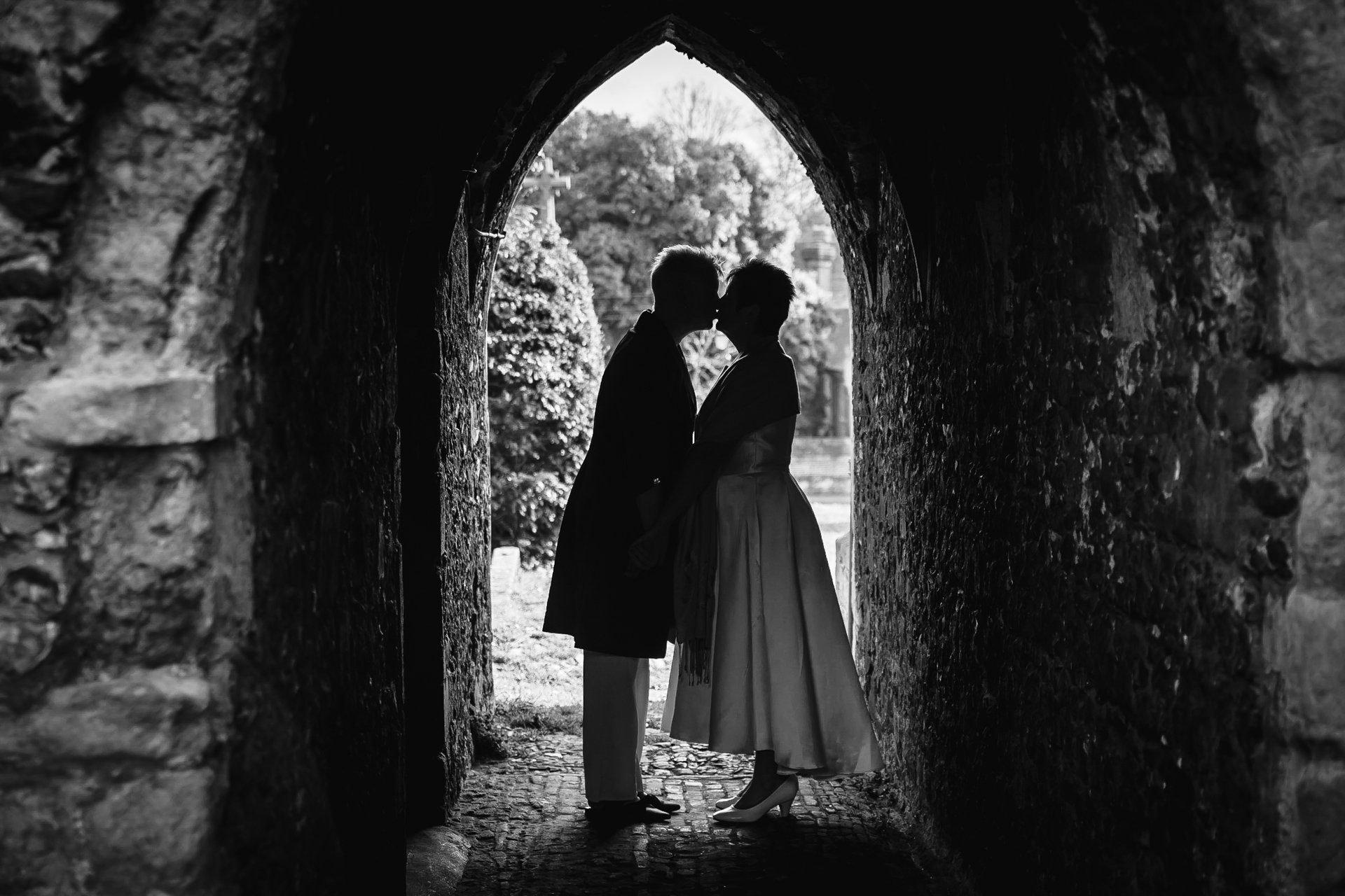 Silhouette of two brides kissing under an arch during bridal portraits