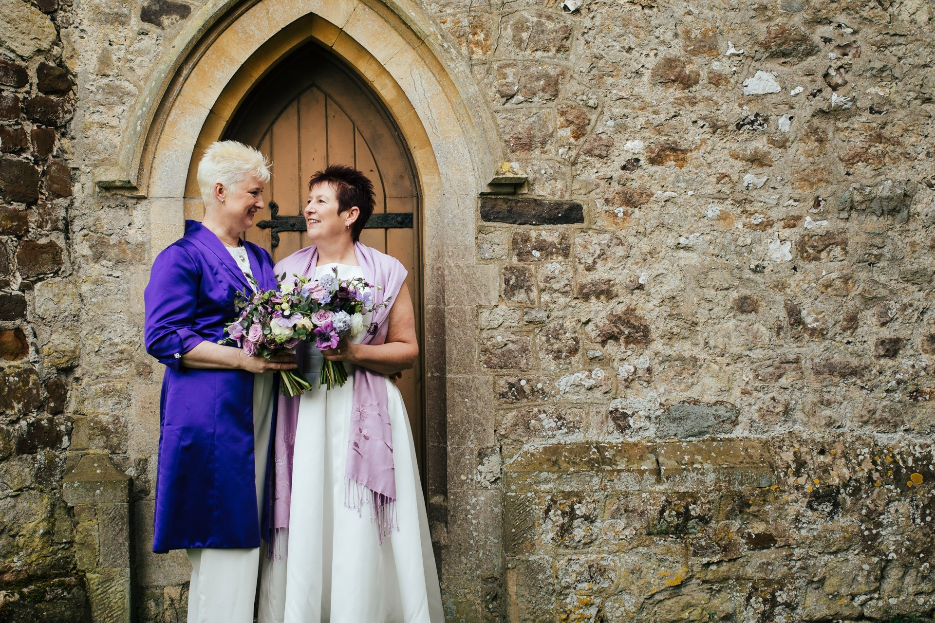 Two brides happy and smiling at each other outside their Kent wedding venue