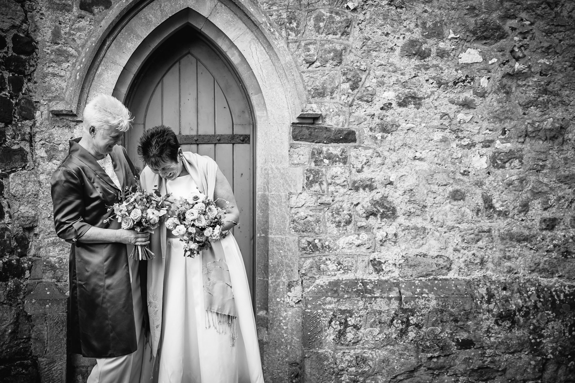 Two brides laughing with each other outside their Kent wedding venue