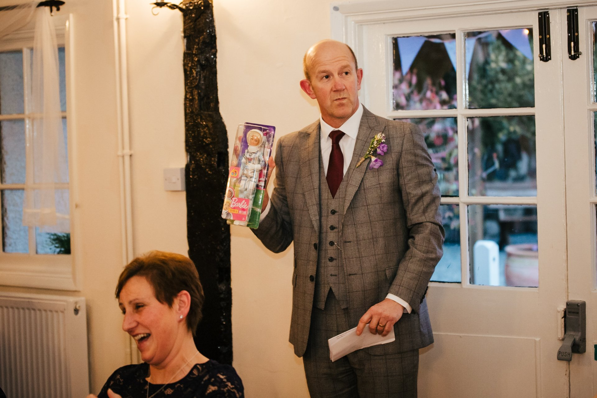 Brides brother holding up barbie doll during wedding speeches
