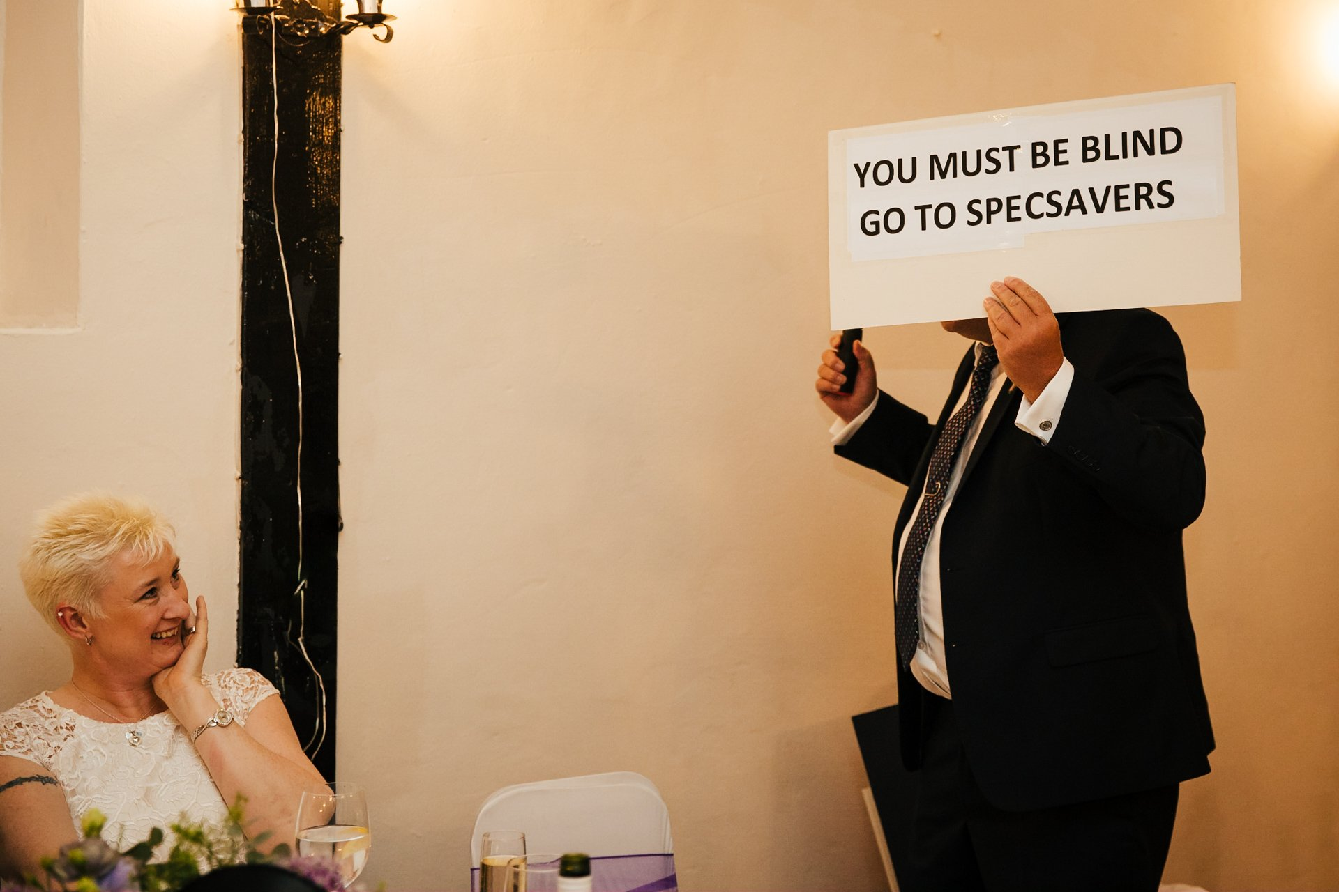Bride brother holding up a sign during their speech