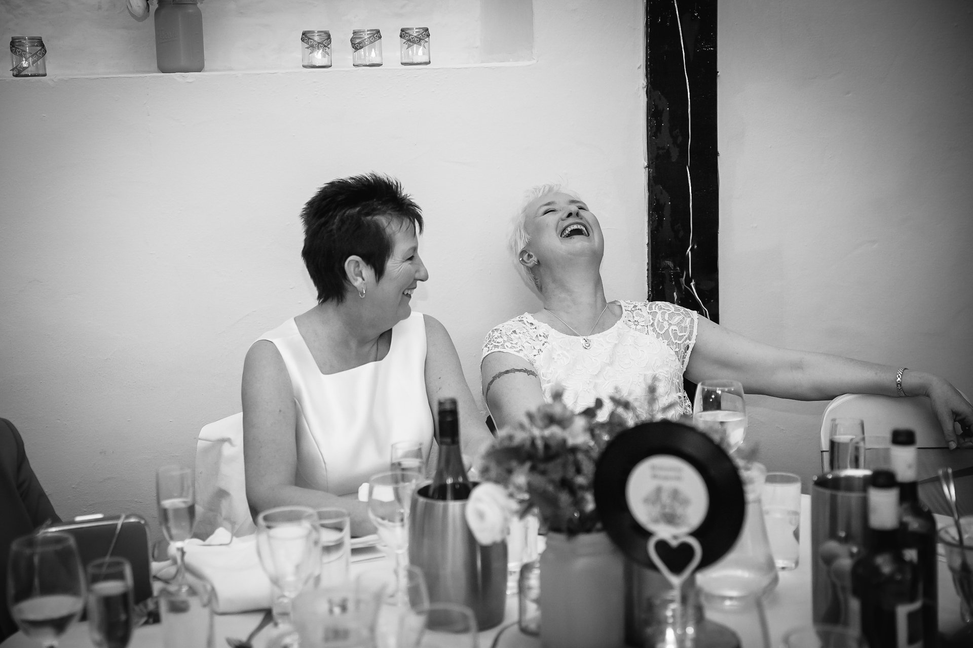 Brides laughing during their wedding speeches