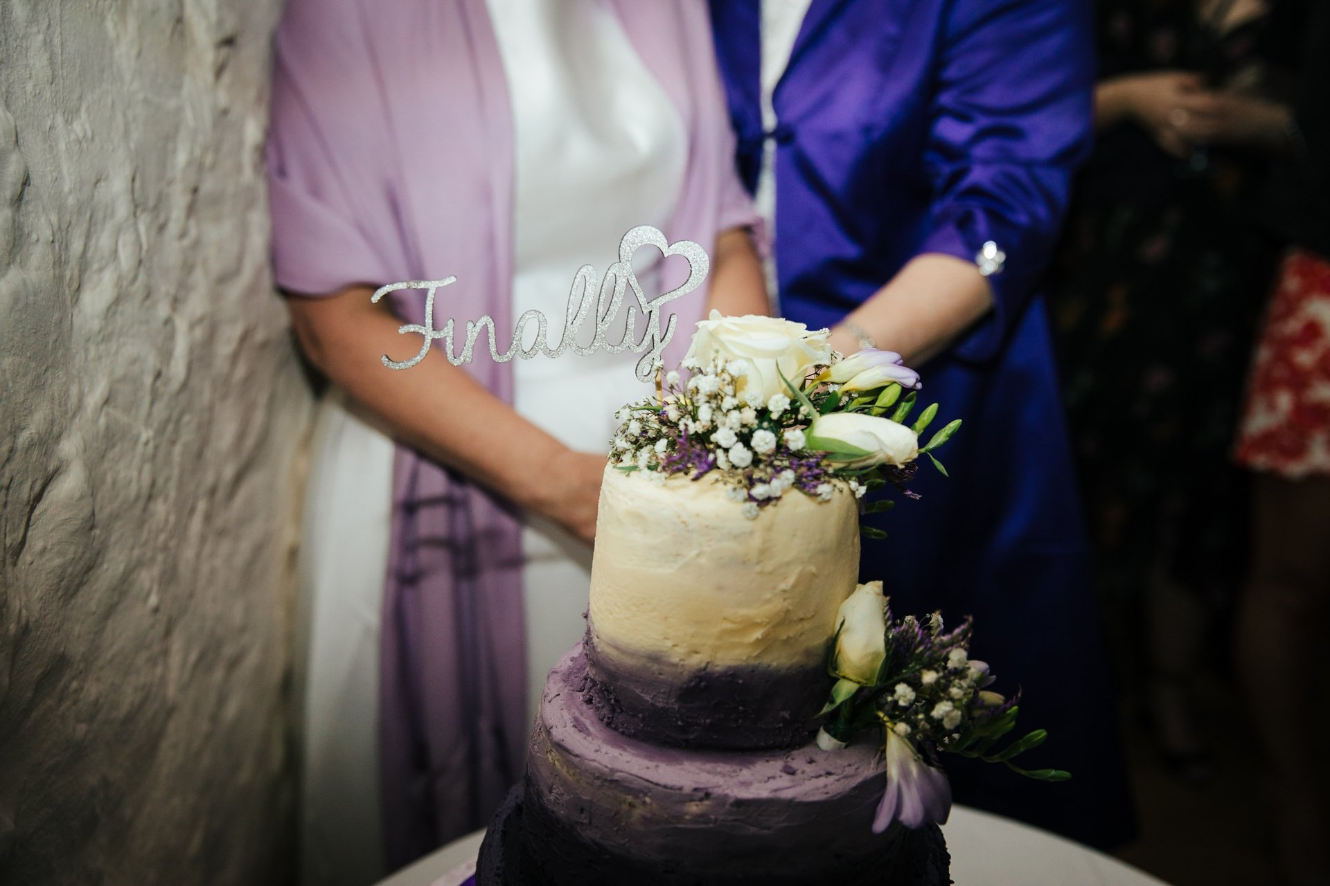 Gorgeous wedding cake with cake topper saying 'finally' with Brides behind