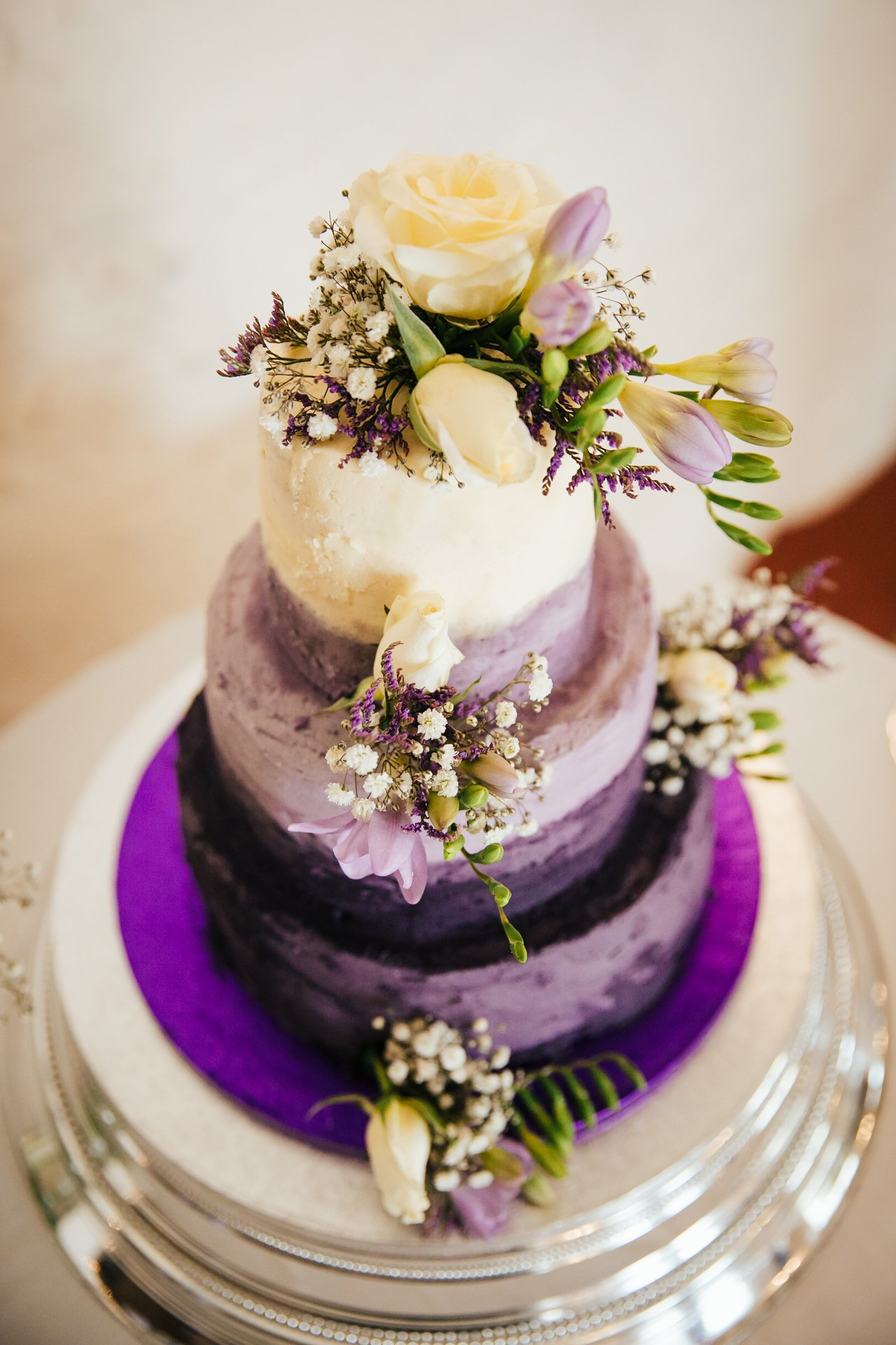 Stunning three tier wedding cake, rustic texture adorned with flowers