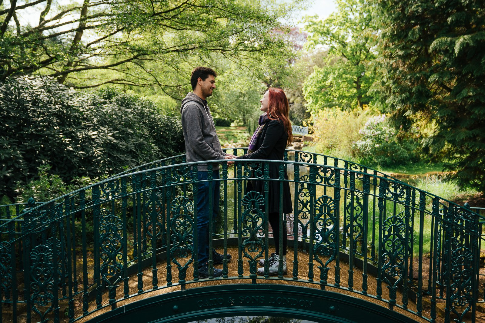 Happy couple holding hands on a bridge in beautiful garden setting