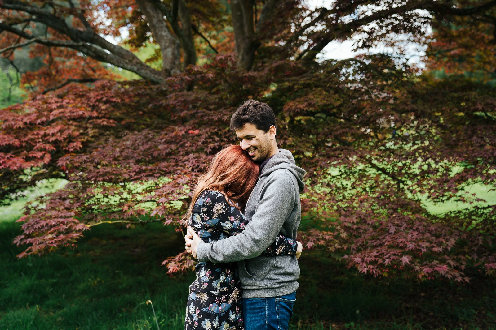 Couple hugging infront of red acer in Swiss Garden pre wedding shoot