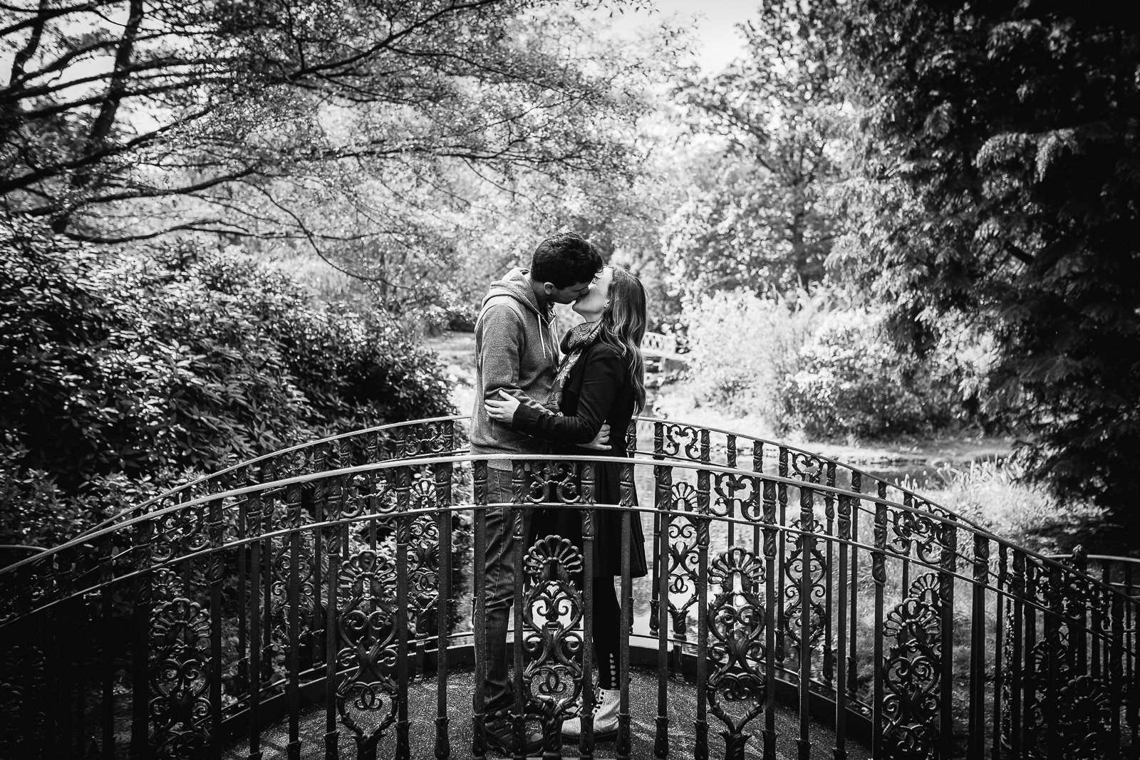 Happy couple kissing on a bridge in beautiful garden setting during their engagement shoot