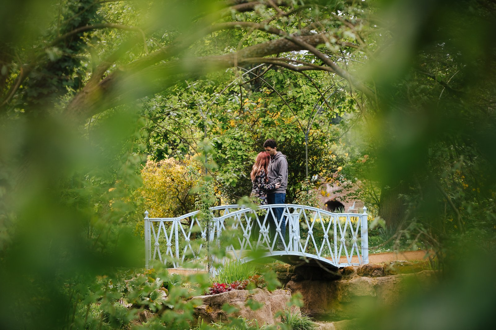 Couple kissing on a bridge through trees at Swiss Gardens Couple shoot