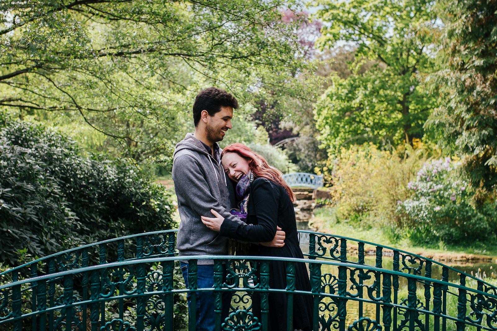 Happy couple hugging and laughing on a bridge in beautiful garden setting