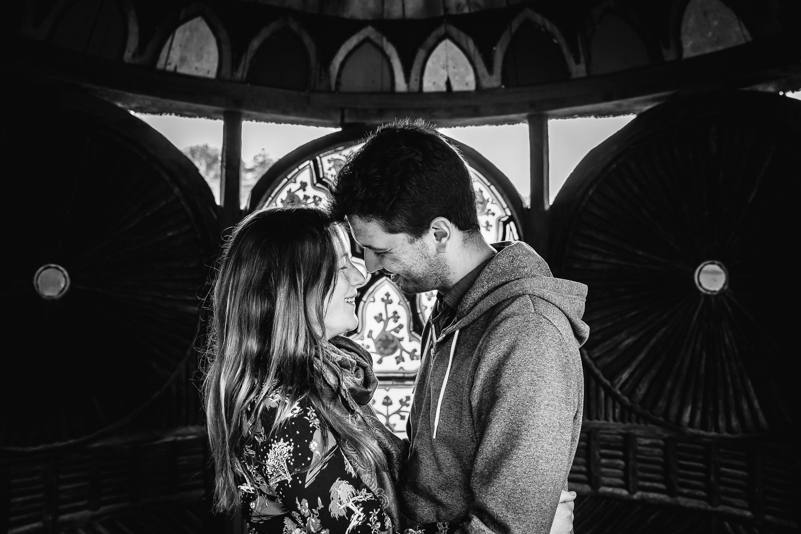 Black and white image of couple about to kiss under Indian Kiosk at Swiss Gardens during their engagement shoot