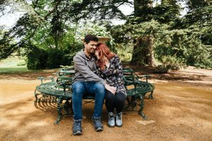 Couple cuddling on green bench in gorgeous Bedfordshire garden setting