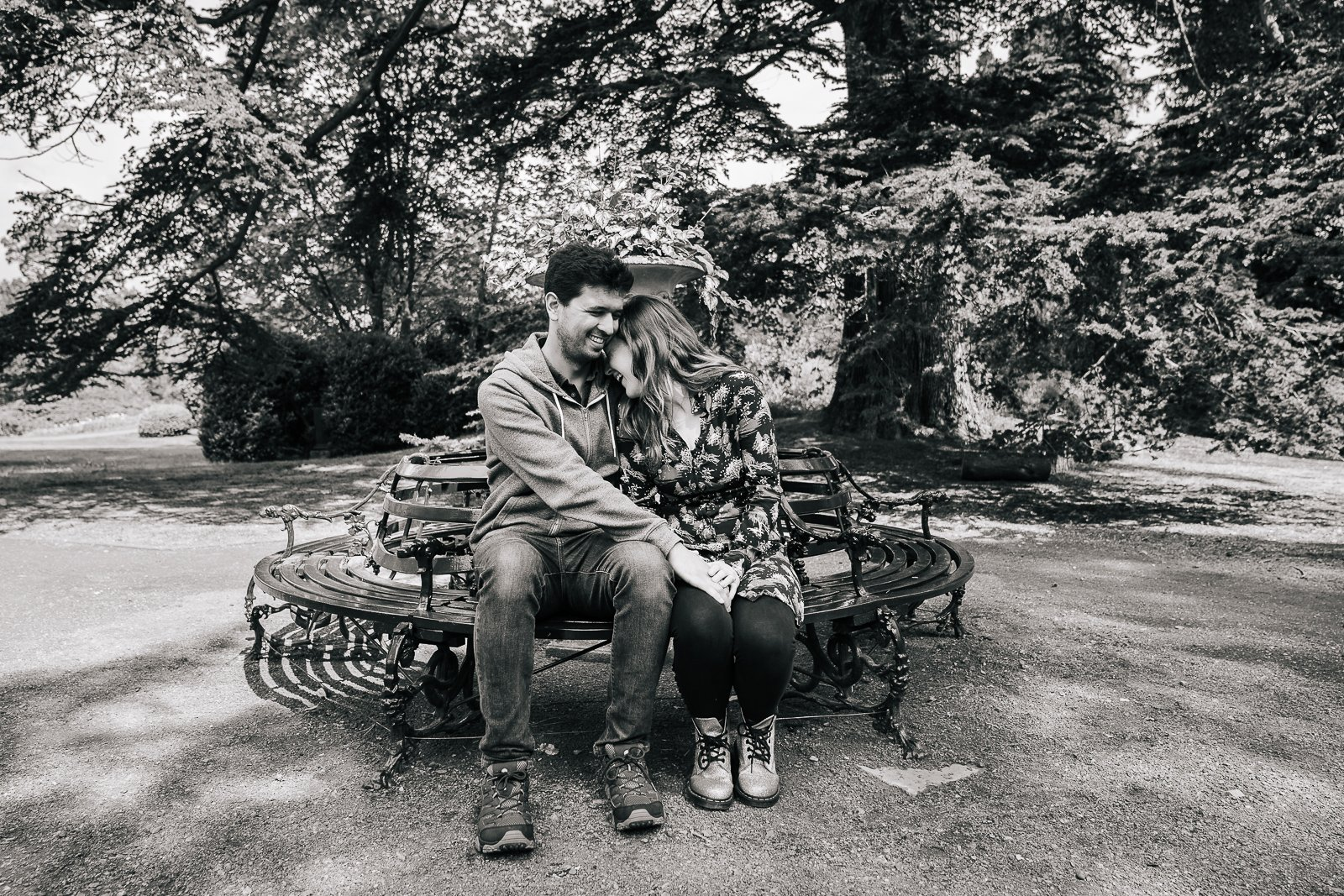 Black and white image of couple cuddling on green bench in gorgeous Bedfordshire garden setting