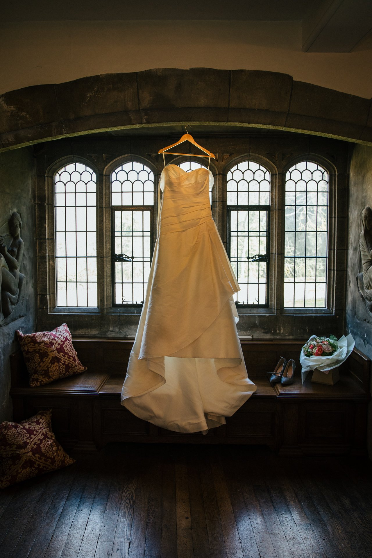 Stunning wedding dress hanging int he window of Allington Castle, Wedding venue Kent