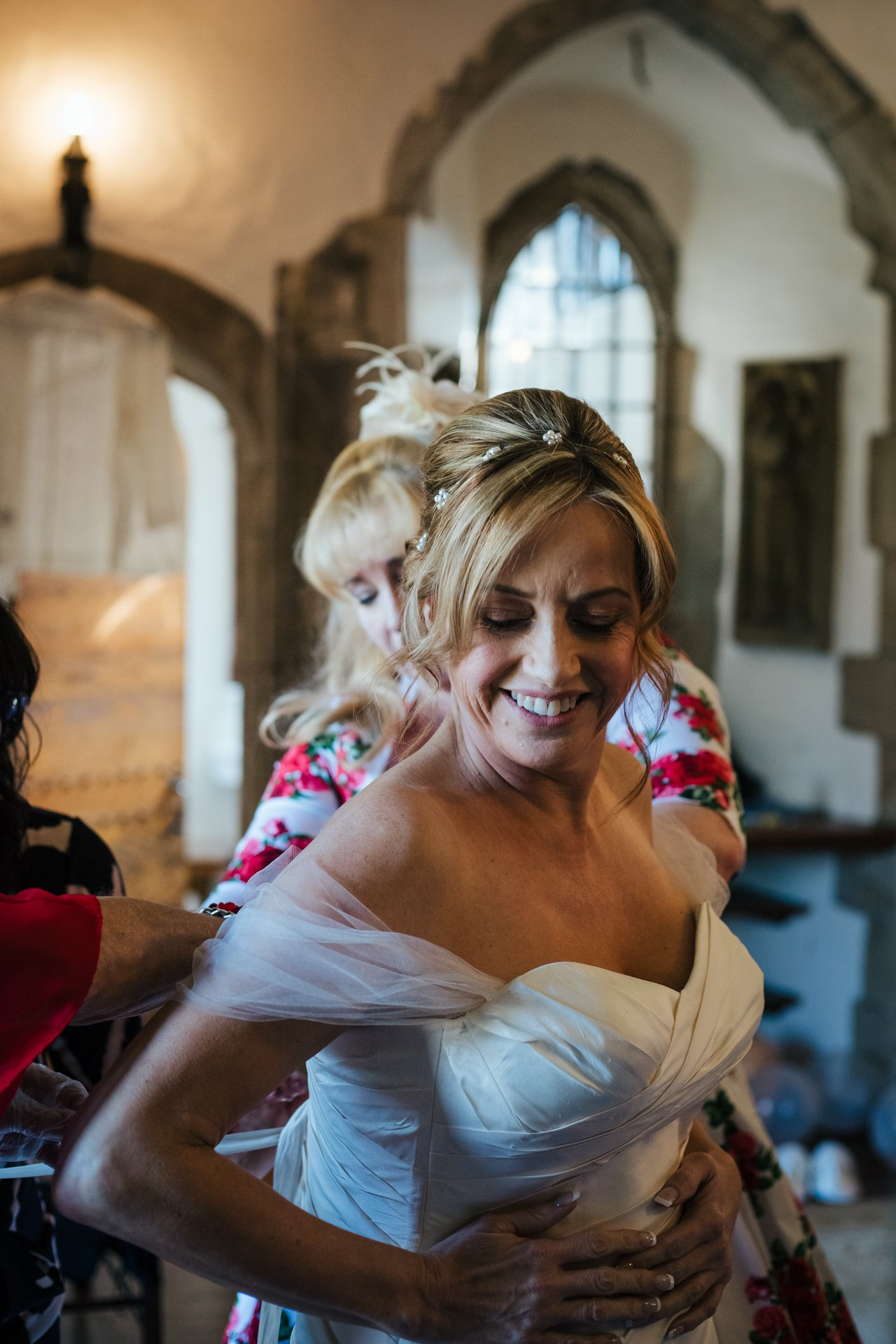 Bride having help doing up her gorgeous wedding dress in Allington Castle, Kent