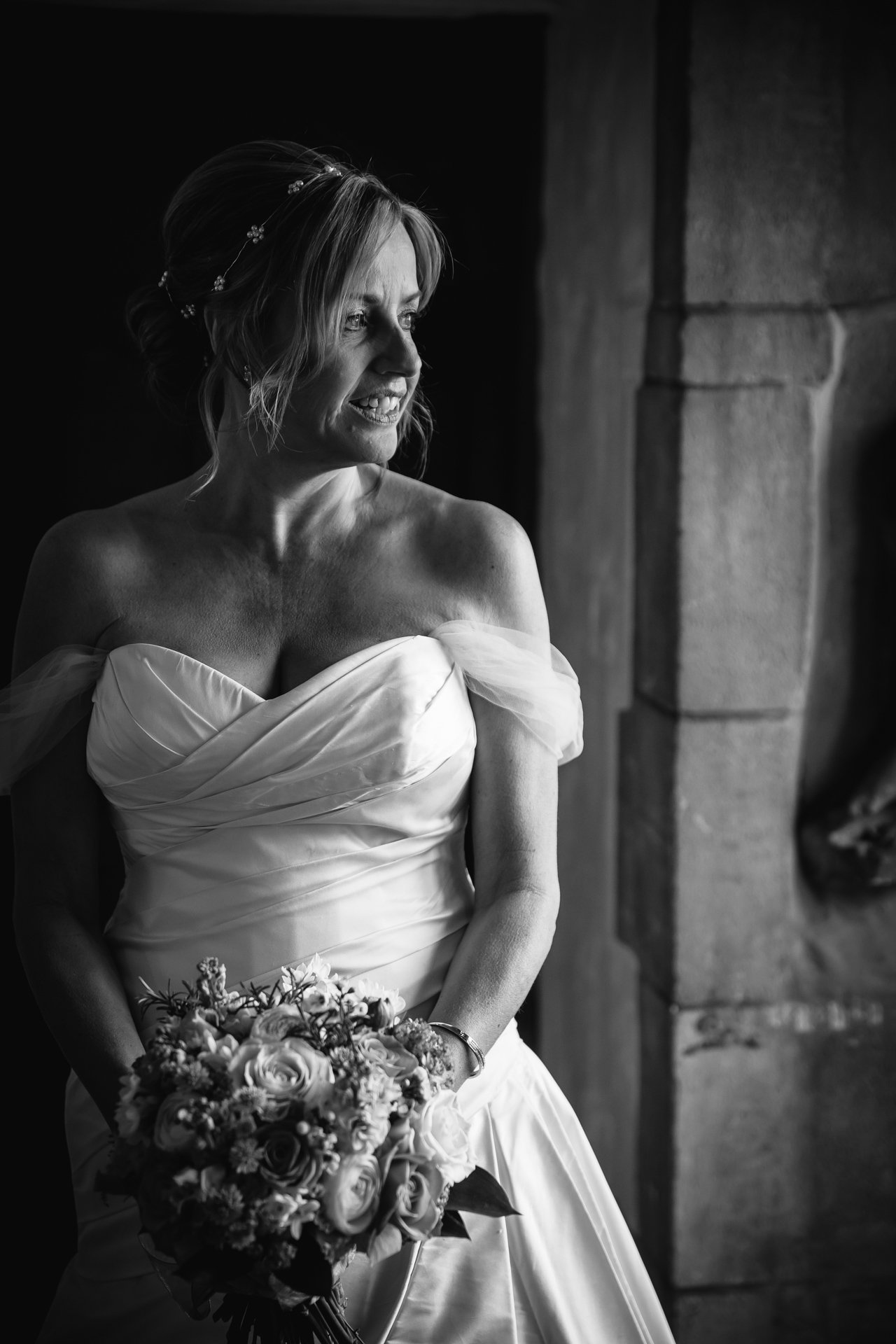 Stunning bride bathed in window light before her wedding at Allington Castle, Kent