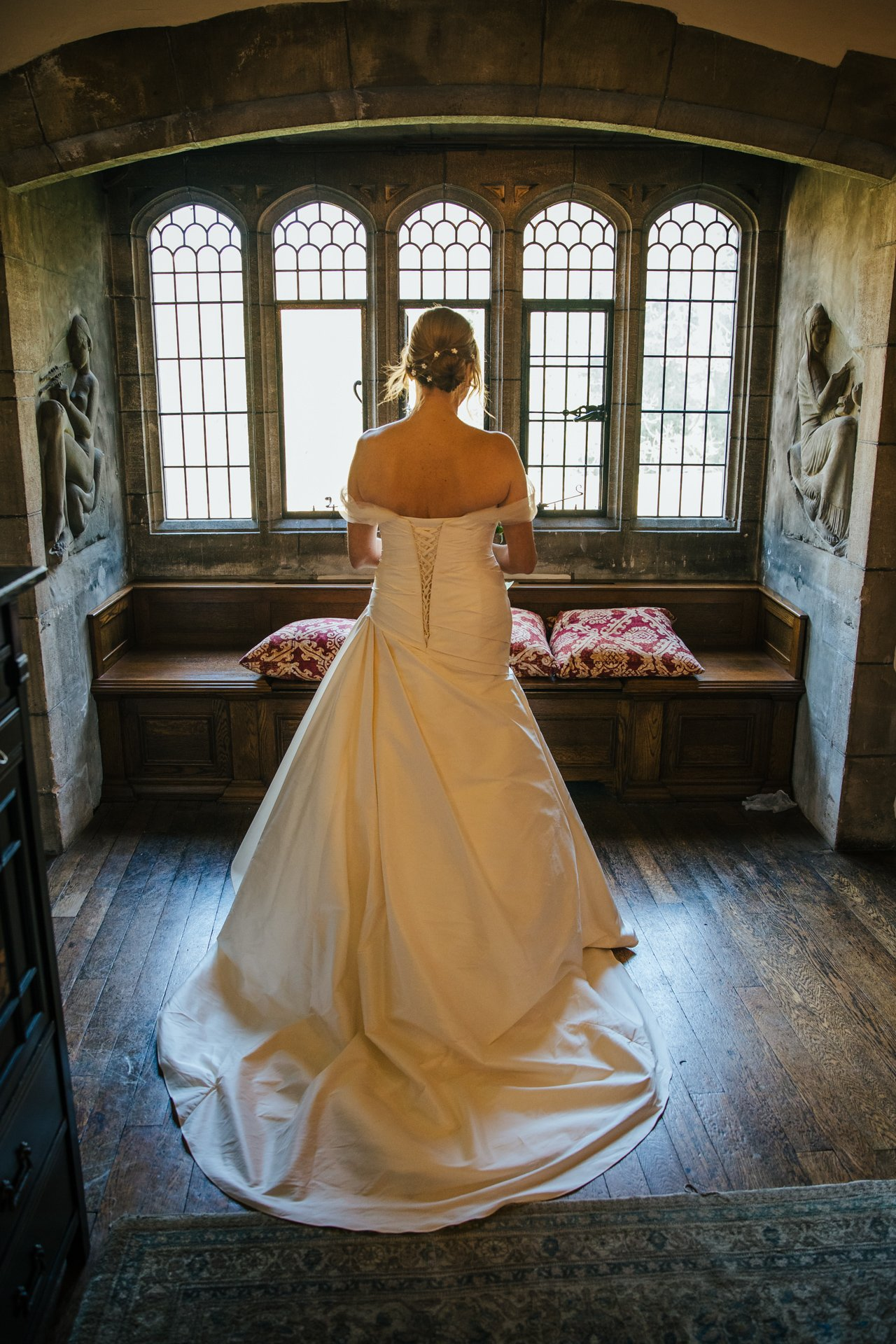 Bride in her wedding dress in front of window in Allington Castle, Kent Wedding Venue