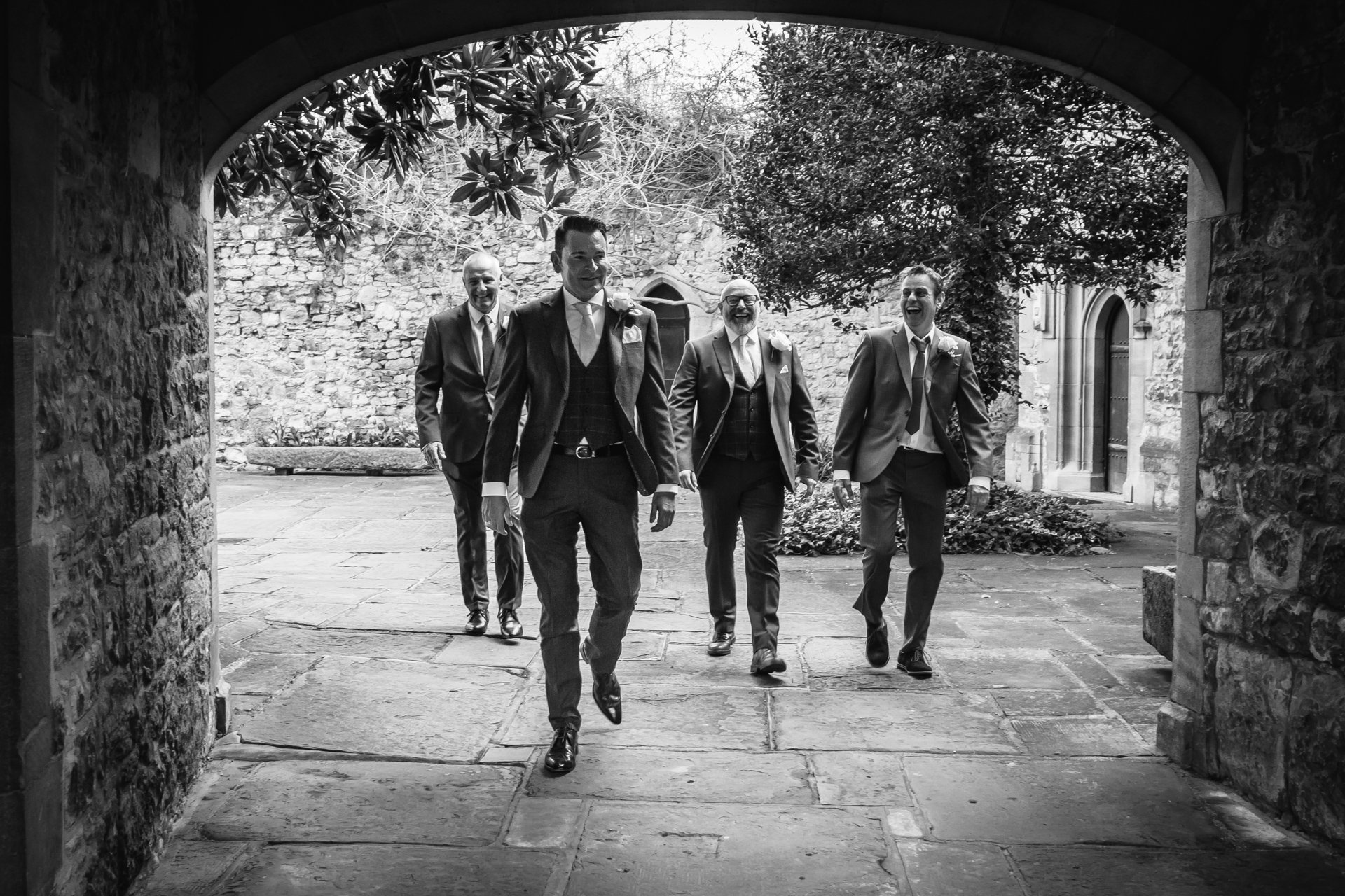 Groom and Groomsmen walking towards camera before his wedding ceremony at Allington Castle