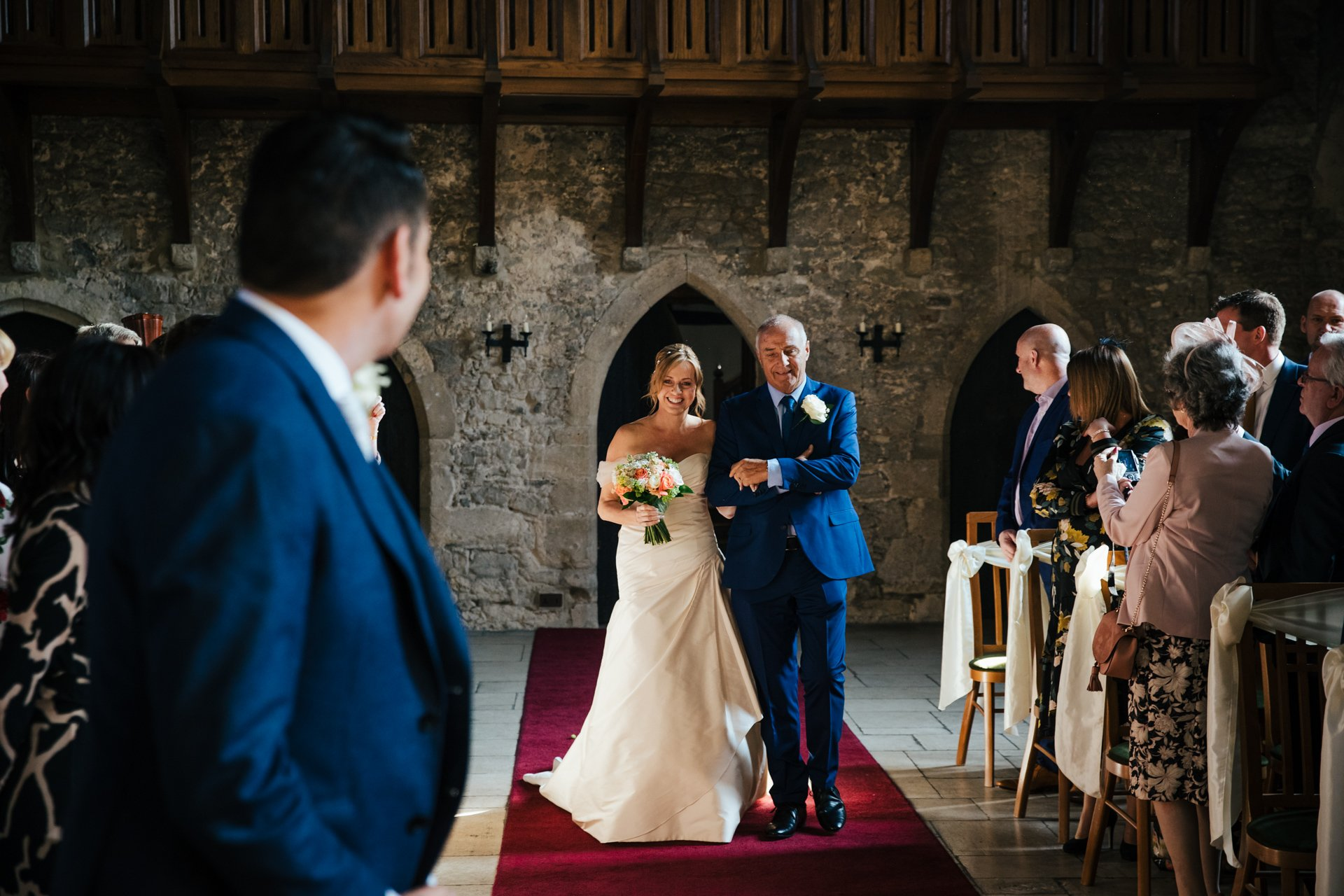 Bride being walked down the aisle by her father towards her groom at Allington Castle, Kent wedding venue