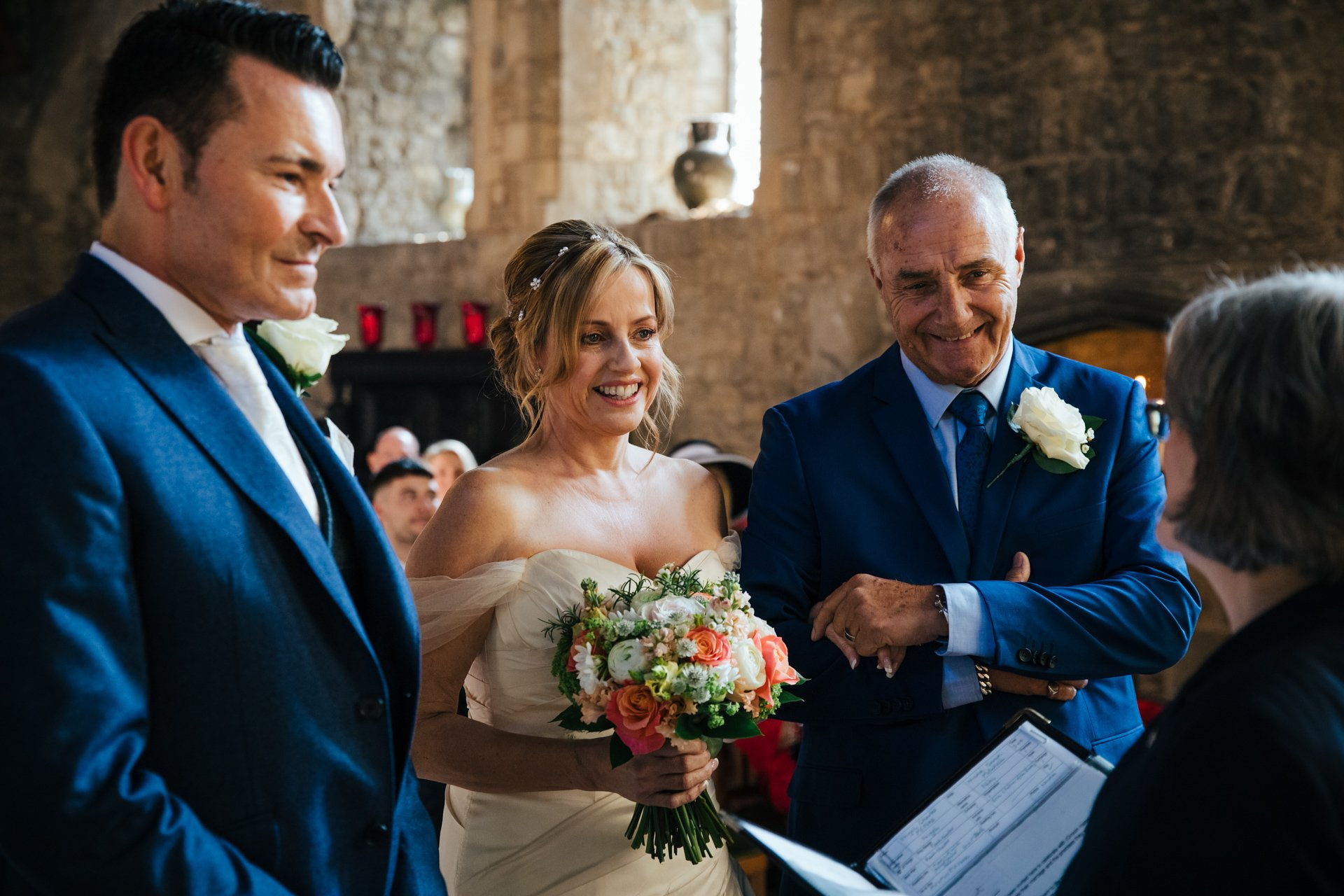 Brides father holding the hand of his daughter next to her groom during ceremony