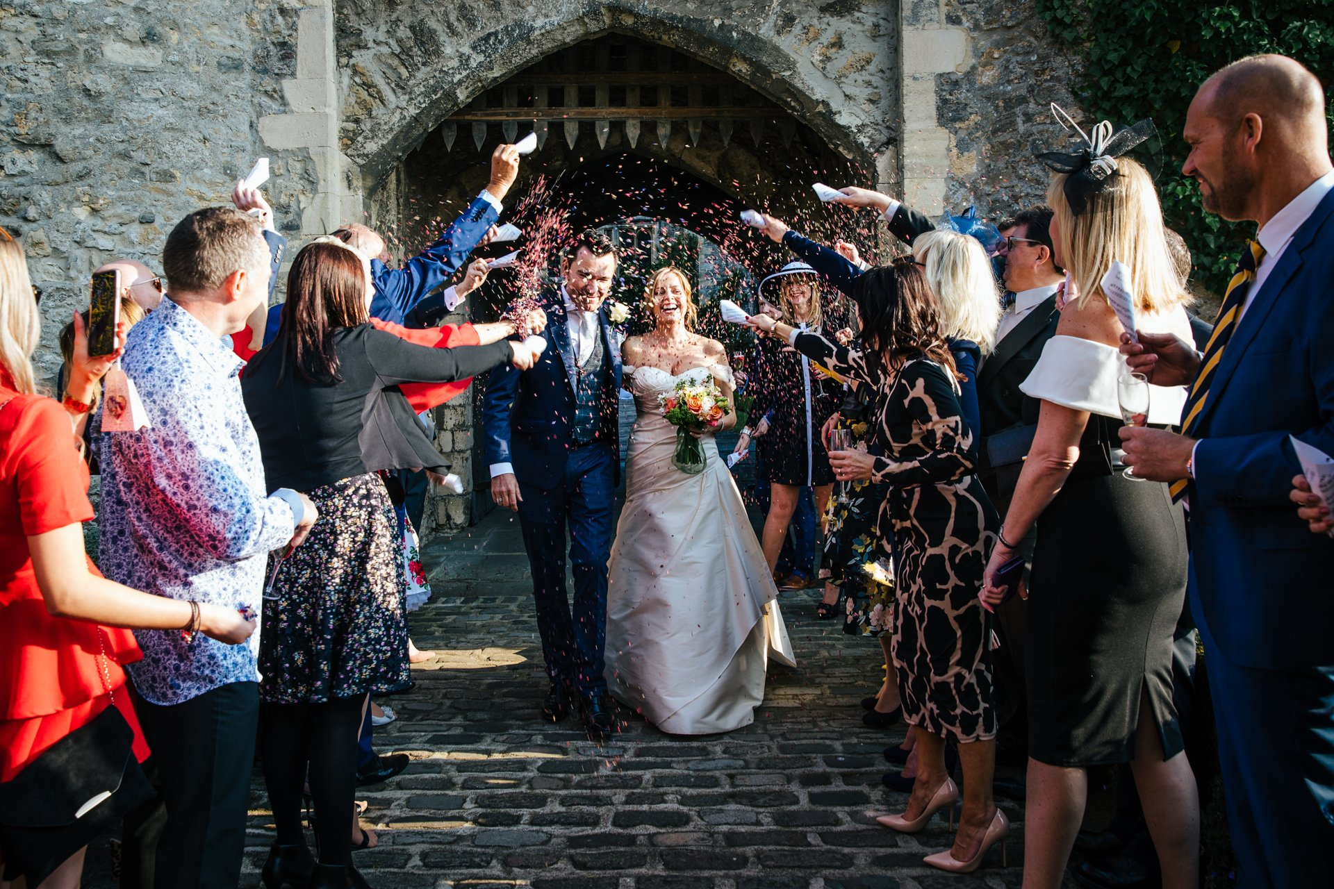 Bride and Groom showered with confetti as they exit their Kent Castle Wedding at Allington