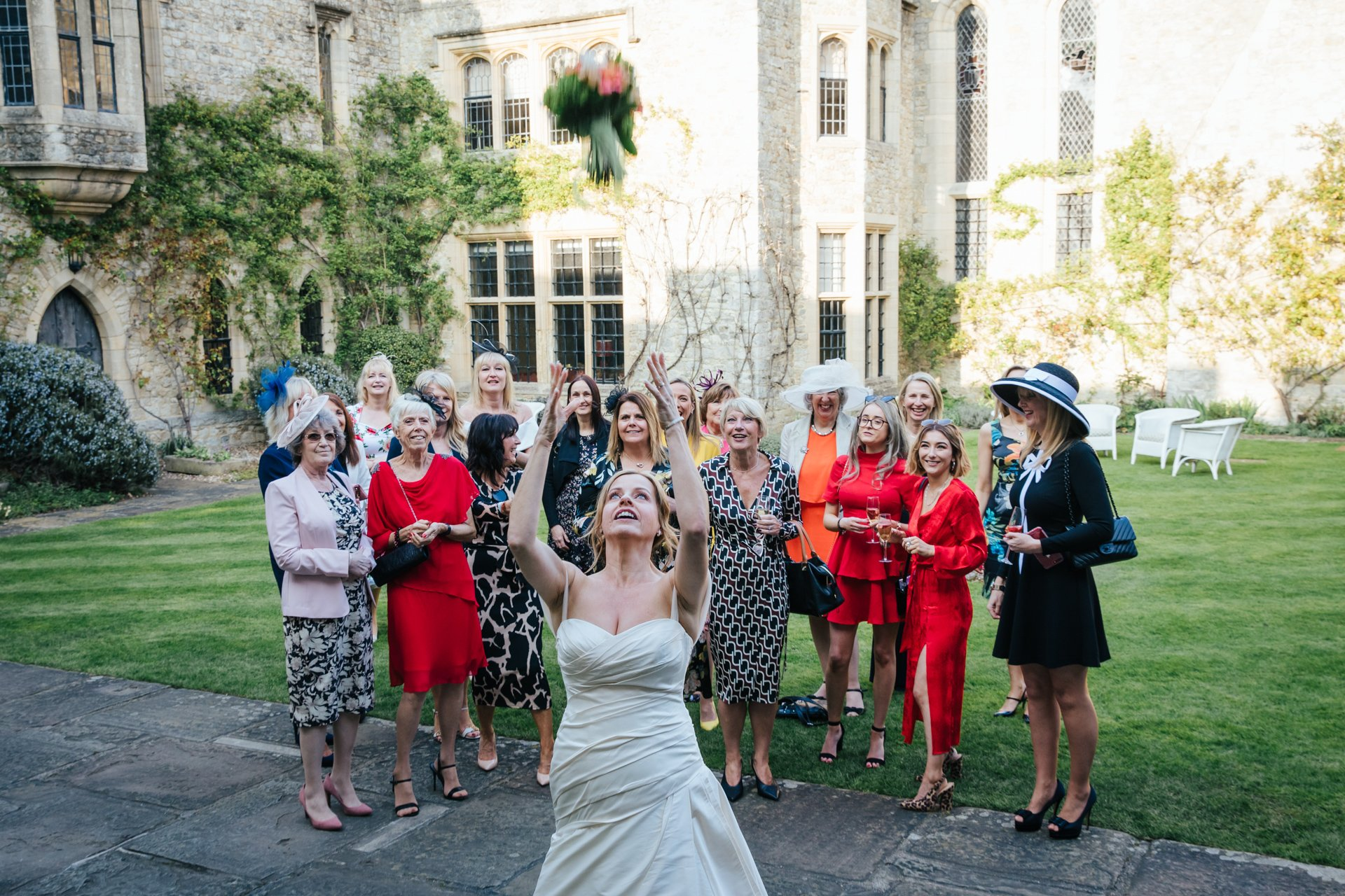 Bride throws her bouquet to her friends in the Courtyard at Allington Castle
