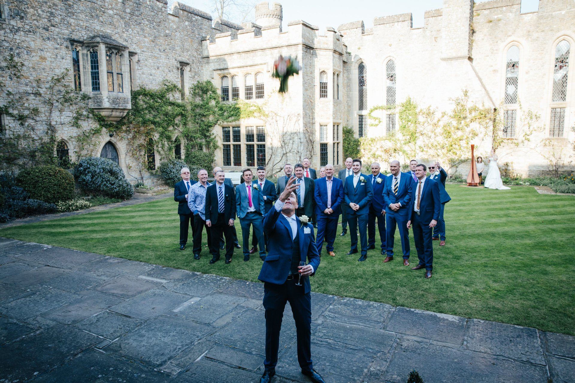 Groom throws brides bouquet to his friends in the Courtyard at Allington Castle